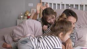 Barnet fostrar läser en saga för hennes älskvärda lilla döttrar som ligger på en säng Ungen ser till och med boken arkivfilmer