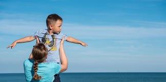 Barnet fostrar med barnsammanträde på bänken nära havshavet Royaltyfria Bilder