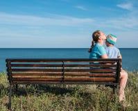 Barnet fostrar med barnsammanträde på bänken nära havshavet Royaltyfri Fotografi