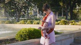 Barnet fostrar med behandla som ett barn i rem genom att använda smartphonen stock video