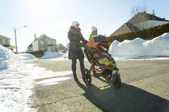 Barnet fostrar med behandla som ett barn i sittvagn går gatavinter Arkivfoton