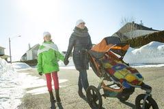 Barnet fostrar med behandla som ett barn i sittvagn går gatavinter Arkivfoto