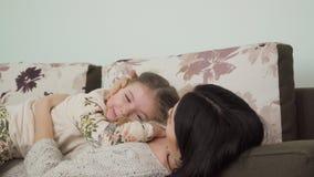 Barnet fostrar med den lilla dottern kopplar av på soffan hemma arkivfilmer