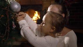 Barnet fostrar med den lilla gulliga dottern som tillsammans dekorerar julgranen arkivfilmer