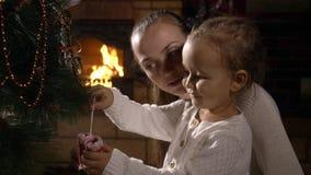 Barnet fostrar med den lilla gulliga dottern som tillsammans dekorerar julgranen lager videofilmer