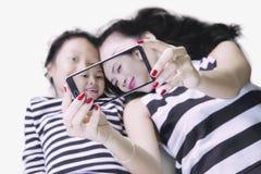 Barnet fostrar med dottern som använder en smartphone Arkivbilder