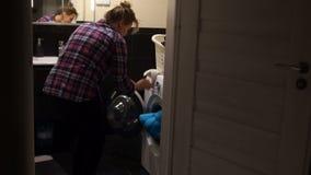 Barnet fostrar med en behandla som ett barnpojke som gör hushållsarbete Den ensamma modern lastar av tvättmaskinen som rymmer eng stock video