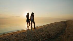 Barnet fostrar med hennes dotter, en tonåring som går på stranden på solnedgången stock video