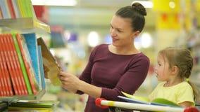 Barnet fostrar med hennes dotter väljer böcker i supermarket Härligt dottersammanträde i en supermarketvagn och stock video