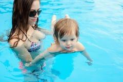 Barnet fostrar med hennes lilla dotter i pölen royaltyfri foto