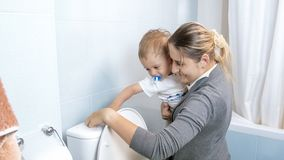 Barnet fostrar med hennes litet barnpojke som spolar vatten i toalett, når de har använt den Arkivfoto