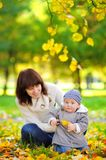 Barnet fostrar med hennes litet behandla som ett barn i hösten parkerar Royaltyfri Bild
