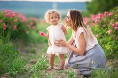 Barnet fostrar med hennes nätta lockiga dotter går i vårträdgården med blommor för rosa färgblomningrosor, solnedgångtid Royaltyfria Bilder
