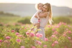 Barnet fostrar med hennes nätta lockiga dotter går i vårträdgården med blommor för rosa färgblomningrosor, solnedgångtid Arkivbild