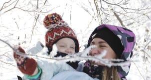Barnet fostrar med hennes son som har gyckel i parkera i vinter arkivfilmer