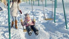 Barnet fostrar med barnet som svänger på gungauppsättningen som är utomhus- i vinter, parkerar Snö som faller, snöfall, vintertid