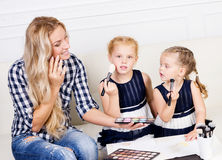 Barnet fostrar med två härliga döttrar med sminkpaletten Royaltyfria Foton