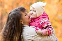 Barnet fostrar med ungeflickan utomhus i höst Royaltyfri Foto