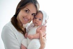 Barnet fostrar och att kyssa hennes nyfött behandla som ett barn pojken hemma, mamman och behandla som ett barn Royaltyfri Bild