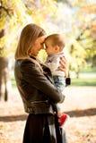 Barnet fostrar och behandla som ett barn pojken i höst parkerar Royaltyfri Fotografi