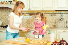 Barnet fostrar, och den gulliga lilla dottern bakar kakor och hagyckel i köket Royaltyfri Fotografi