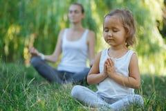 Barnet fostrar, och den gulliga lilla dottern som mediterar i lotusblomma, poserar tillsammans Royaltyfria Foton