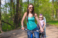 Barnet fostrar, och den gulliga lilla dotterridningen cyklar tillsammans Royaltyfria Foton