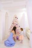 Barnet fostrar och den lilla dottern som dekorerar julgranen och p Arkivfoton