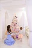 Barnet fostrar och den lilla dottern som dekorerar julgranen och p Arkivbilder