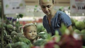 Barnet fostrar och den lilla dottern som väljer frukter på supermarket