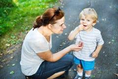 Barnet fostrar och den lilla litet barnpojken som äter lösa bär i för Arkivbild