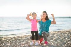 Barnet fostrar och dottern i konditionkugghjul på stranden som böjer armar Arkivfoto