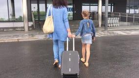Barnet fostrar, och dottern med den turist- dräkten går till sikten för flygplatsresväskabaksida arkivfilmer