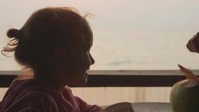 Barnet fostrar, och dottern sitter på seaviewkafét och dricker kokosnötter tillsammans stock video
