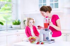 Barnet fostrar och dottern som gör jiuce för ny frukt Arkivfoton