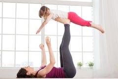 Barnet fostrar och dottern som gör yogaövning Arkivbild