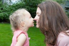 Barnet fostrar och hennes åriga dotter som omfamnar och kysser Arkivbild