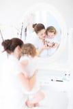 Barnet fostrar och hennes dotter som applicerar smink fotografering för bildbyråer