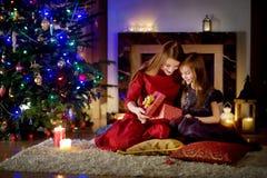 Barnet fostrar och hennes dotter som packar upp julgåvor vid en spis i en hemtrevlig mörk vardagsrum på jul royaltyfri fotografi