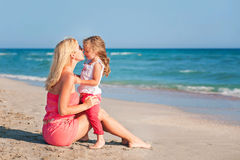 Barnet fostrar och hennes förtjusande dotter som tycker om dag på stranden Royaltyfri Foto