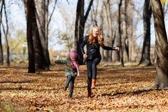Barnet fostrar, och hennes flicka i höst parkerar Royaltyfri Bild