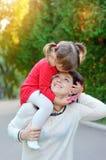 Barnet fostrar, och hennes gulliga flicka har gyckel i höstvingård Royaltyfri Fotografi