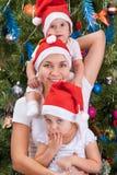 Barnet fostrar och hennes lilla döttrar nära till en julgran Royaltyfri Bild