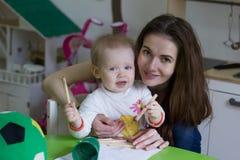 Barnet fostrar och hennes lilla dotter som tillsammans drar royaltyfri fotografi