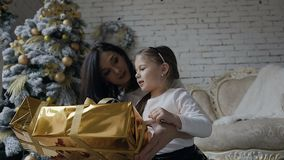 Barnet fostrar och hennes lilla dottersammanträde på golvet nära julgranen och ser gåvorna som packas stock video