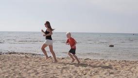 Barnet fostrar och hennes son som g?r p? stranden lager videofilmer