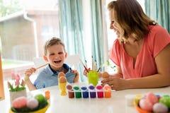 Barnet fostrar och hennes son som har gyckel, medan måla ägg för påsk royaltyfria bilder