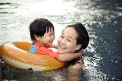 Barnet fostrar och hennes son som har gyckel som spelar tillsammans på simbassängen Royaltyfri Fotografi