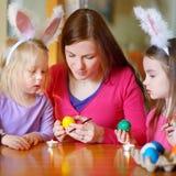 Barnet fostrar och hennes två döttrar som målar påskägg Arkivfoto