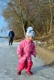 Barnet fostrar och lilla flickan in i solljuset på isen av floden royaltyfri foto